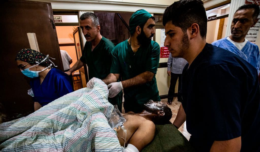 A wounded man receives treatment at a hospital in the northeastern Syrian Kurdish city of Qamishli on October 13, 2019, following a Turkish air strike that hit a convoy of vehicles carrying civilians and journalists. (Photo: DELIL SOULEIMAN/AFP via Getty Images)