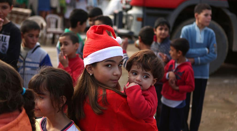 Chloe, a Lebanese Christian teenager dressed as Santa Claus, holds a Syrian refugee on Christmas Eve, 2016 during a gift distribution organised by the Maronite congregation north of Beirut. UN officals in Jordan are blocking Syrian Christian refugees from getting help (Photo: PATRICK BAZ/AFP via Getty Images)