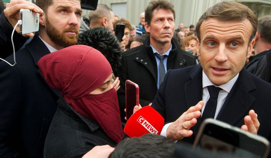 """French President Emmanuel Macron is taking heat after a woman wearing a full-face veil approached him ahead of a speech announcing new measures to fight Islamic """"separatism"""" in France. France was the first European country to ban the wearing of niqabs in public (Photo: SEBASTIEN BOZON/POOL/AFP via Getty Images)"""