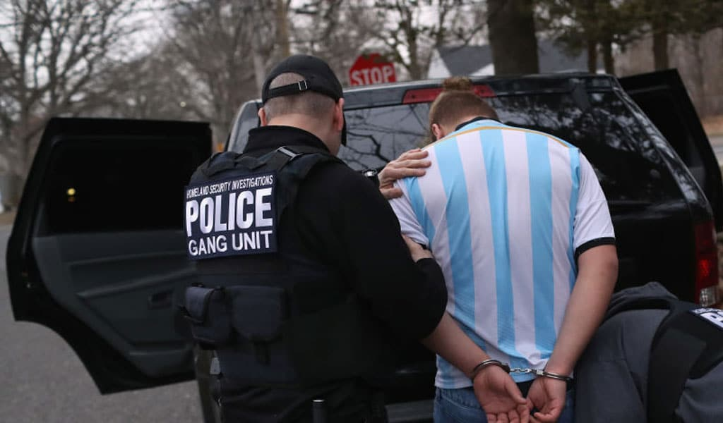Homeland Security ICE agents frisk a suspected MS-13 gang member and Honduran immigrant after arresting him at his home on March 29, 2018 in Brentwood, New York. The actions were part of Operation Matador, a nearly year-long anti-gang effort targeting transnational gangs, with an emphasis on MS-13. Under the New Way Forward Act, such individuals would be be deported or possibly even arrested. (Photo by John Moore/Getty Images)