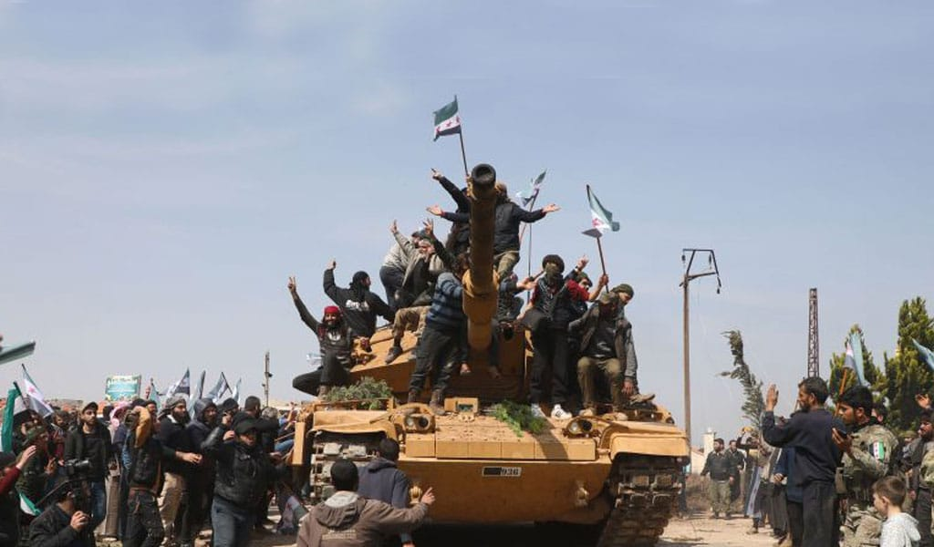 Syrians climb atop a Turkish tank in protest. Turkey has used the situation in Syria to attack the Syrian Kurds. The Syrian Defense Forces, led by Kurds, say that containing ISIS prisoners puts an undue burden on them in their fight for survival (Photo: AAREF WATAD/AFP via Getty Images)