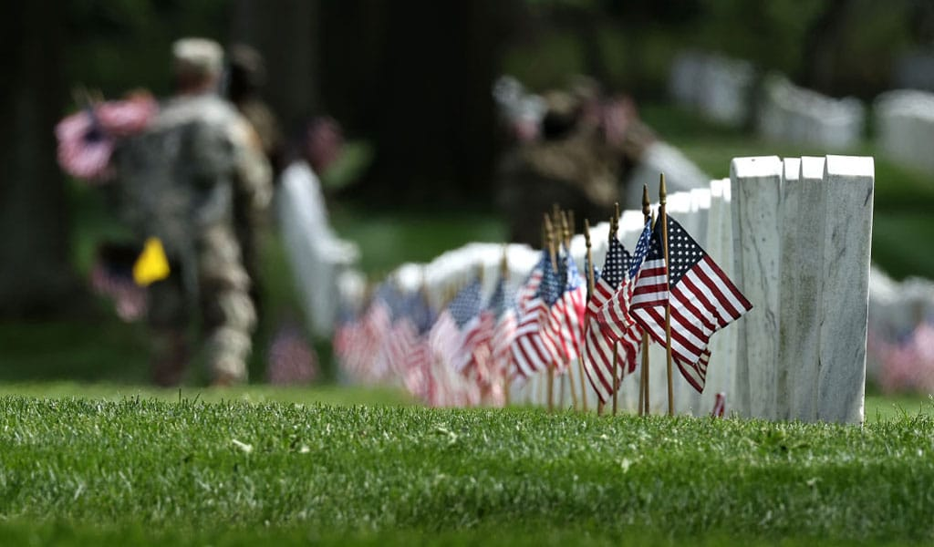 Soldiers from the 3rd Infantry Regiment place American flags on each grave at Arlington National Cemetery ahead of Memorail Day (Photo: Chip Somodevilla/Getty Images)