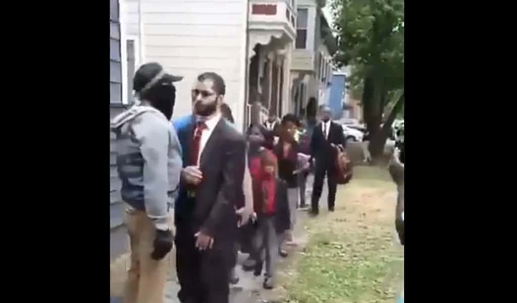 A BLM protester attempts to stop a line of worshipers from entering the Grace Baptist Burch in Troy, NY (Photo: Twitter)