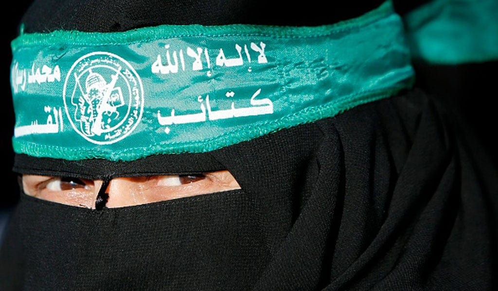 A Palestinian woman wearing a headband with the emblem of Hamas' military wing protests in Gaza (Illustrative photo: MOHAMMED ABED/AFP via Getty Images)