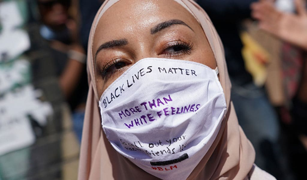 "A Muslim woman wears a face mask that reads: ""Black lives matter more than white feelings"" at a protest rally in Berlin, Germany. BLM and Islamism are now part of intersectional politics (Photo by Sean Gallup/Getty Images)"