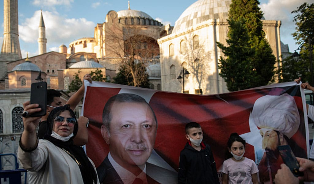 People pose for photographs in front of a picture of Turkey's President Tayyip Erdogan and Ottoman Sultan Mehmet II outside Istanbul's Hagia Sophia after the Turkish government turned the historic cathedral into a mosque. (Photo: Burak Kara/Getty Images)