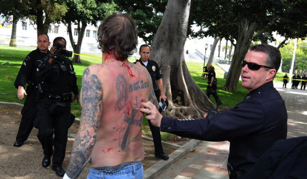 Police remove a man with Nazi skin tattoos after he was beaten by an angry crowd of counterprotesters at the American National Socialist Movement rally in front of the Los Angeles City Hall April 17, 2010. (Photo; MARK RALSTON/AFP via Getty Images)