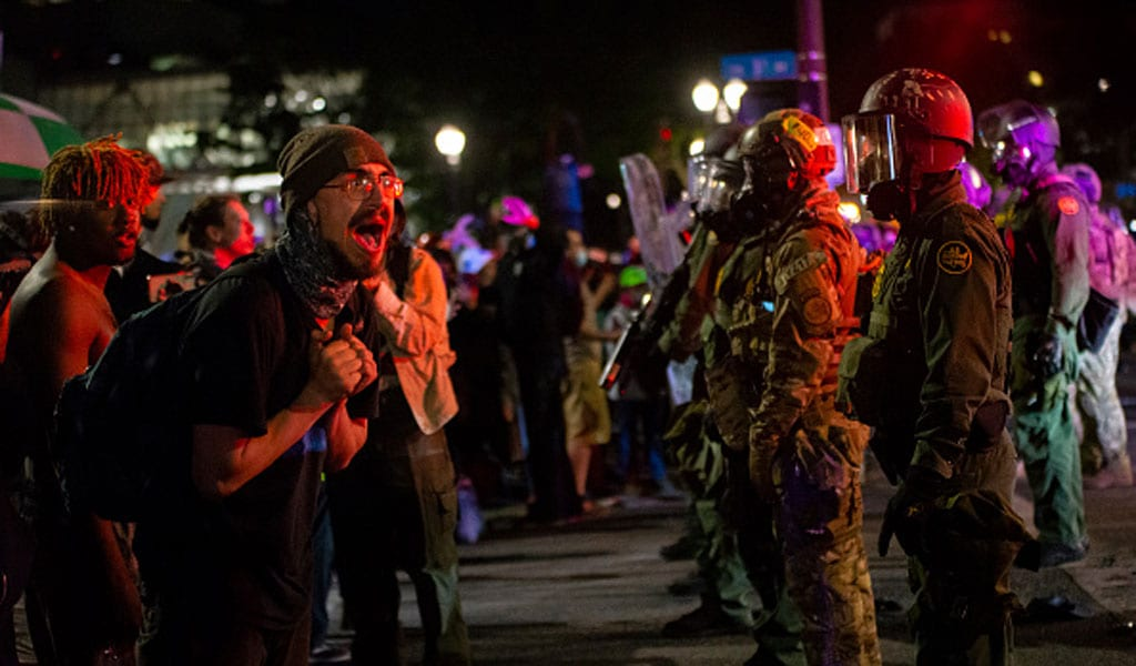 A protester in Portland screams at a federal agent (Photo: Nathan Howard/Getty Images)