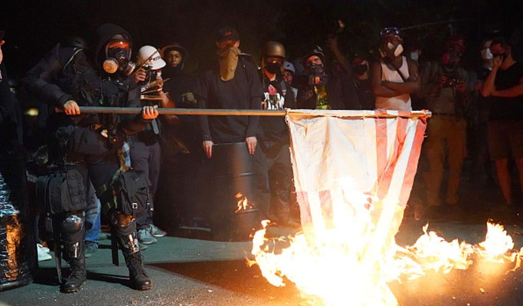 Protesters in Portland burn an American flag (Photo: Nathan Howard/Getty Images)