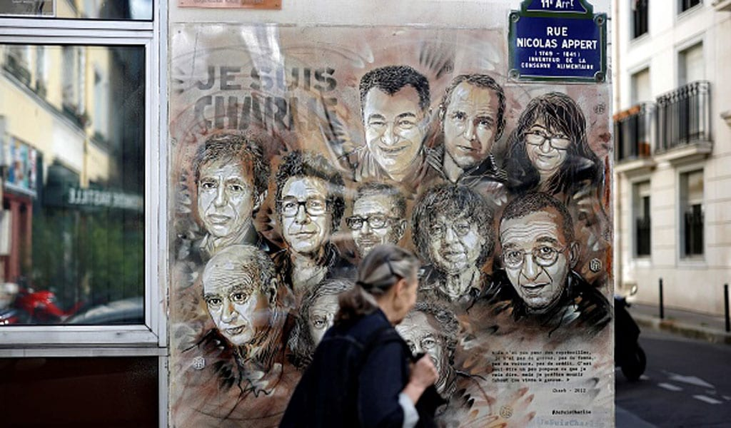 A woman walks past a painting by French street artist and painter Christian Guemy, known as C215, in tribute to members of Charlie Hebdo magazine who were killed by jihadist gunmen in Paris on January 2015. Fourteen accused accomplices in the attacks on the both Charlie Hebdo and a kosher supermarket and in the Paris of Montrouge go on trial on September 2. 2020 ((Photo: THOMAS COEX/AFP via Getty Images)