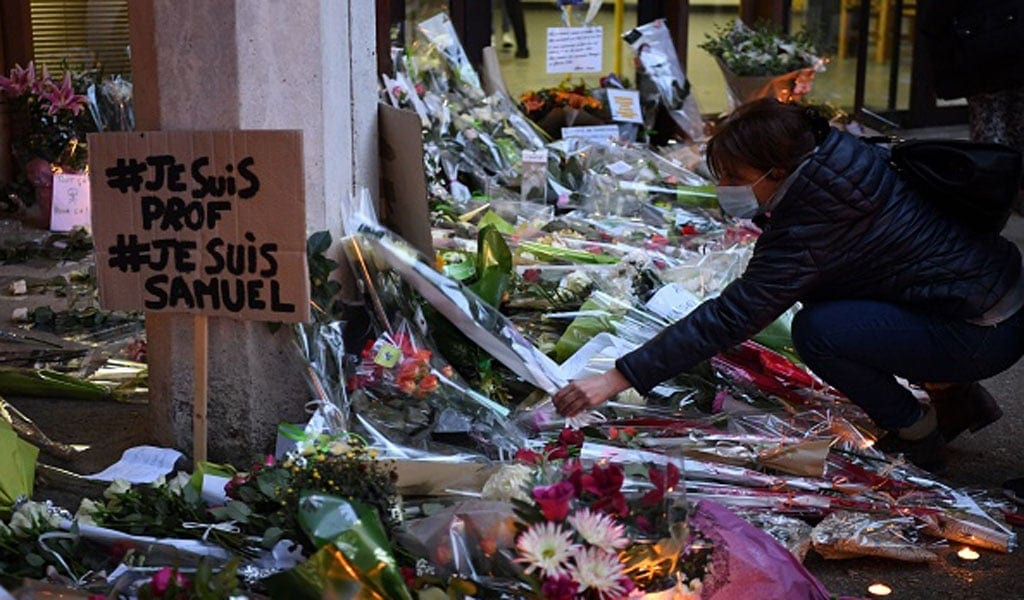 A woman lays flowers next to a poster reading 'I am a teacher, I am Samuel' at the entrance of the school in Conflans-Sainte-Honorine, 20 miles from Paris where schoolteacher Samuel Paty was beheaded in an Islamist terror attack (Photo:BERTRAND GUAY/AFP via Getty Images)