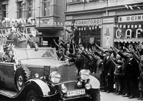 October 1, 1938: Adolf Hitler is greeted with the Nazi salute as he heads a convoy through Sudetenland, which had become part of the Third Reich after the Munich Pact. (Photo: Topical Press Agency/Getty Images)