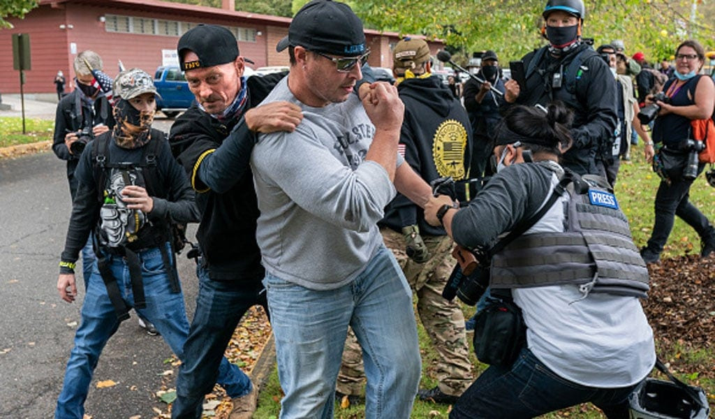 A member of the Proud Boys scuffles with a journalist in Portland, Oregon while another member of the group tries to break up the fight (Photo: Nathan Howard/Getty Images)