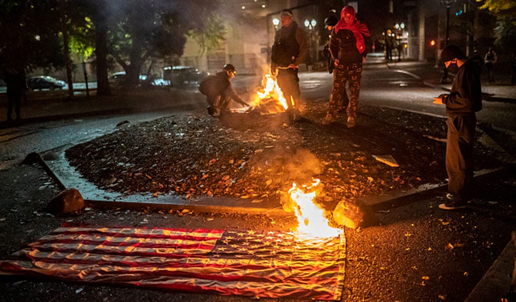 Protesters in Portland burn the American flag on election night (Photo: Nathan Howard/Getty Images)